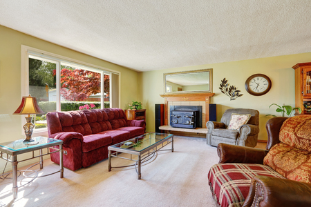 fireplace family: Retro style family room interior with comfortable red sofa, large window and vintage fireplace. Northwest, USA