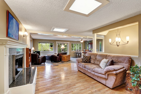 Open plan family room with hardwood floor, fireplace, skylights on the ceiling and mocha couch. Northwest, USA Stock Photo
