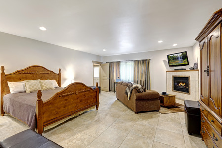House interior with open floor plan. Living room and bedroom with  White walls and beige tile floor. Northwest, USA