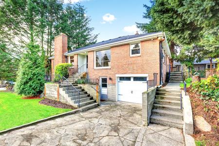 Amerikanischen roten Backstein zweistöckiges Haus außen mit Garage und auch um gepflegten Garten. Northwest, USA