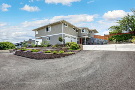 Luxury house exterior with natural stone design, double doors garage and wide concrete driveway. Northwest, USA