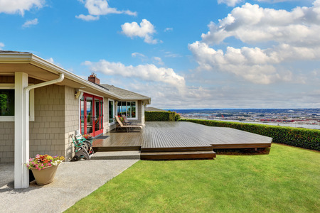 Luxury house exterior with large wooden walkout deck and panoramic view of Tacoma city. Northwest, USA