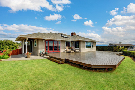 Luxury house exterior with large wooden walkout deck and blue sky background. Northwest, USA Stock Photo