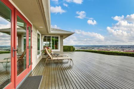 Luxe huis exterieur met grote houten uitloop dek en blauwe hemel achtergrond. Noordwest, Verenigde Staten