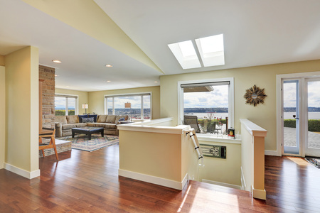 Open plan house interior with hardwood floor, staircase to downstairs, view of family area and vaulted ceiling with skylights. Northwest, USA