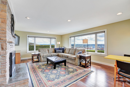 Cozy family room with stone brick wall , colorful rug, corner sofa set and amazing view from the windows. Northwest, USA