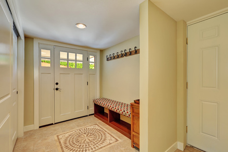 entryway: Entryway in light tones with mosaic tile floor, bench seat, built-in wardrobe and hangers on the wall. Northwest, USA