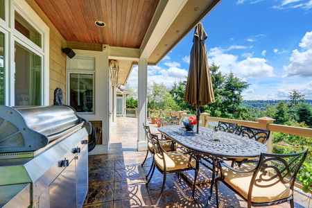 Gorgeous view from luxury house terrace with patio table set, barbecue and stone floor . Northwest, USA Reklamní fotografie