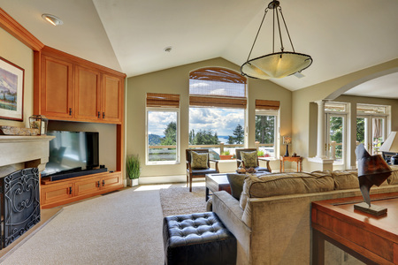 Vaulted ceiling living room with large windows overlooking beautiful view, interior of luxury house. Northwest, USA