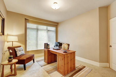 home office interior: Interior of home office with beige walls and wooden desk in luxurious house. Northwest, USA