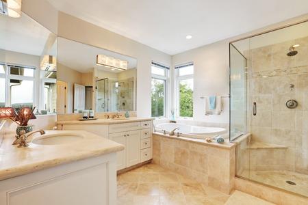 Master badkamer interieur met beige tegelvloer, dubbele wastafel, bad en glazen douche. Noordwest, Verenigde Staten Stockfoto