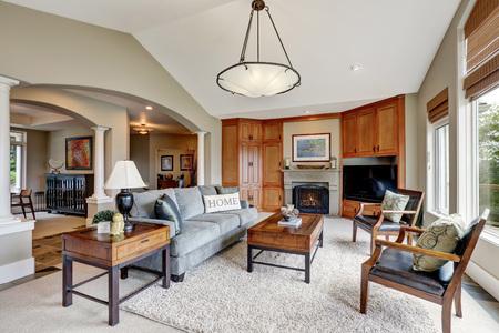 Interior de la sala de estar clásica con grandes ventanas, arcos y techo abovedado en la casa de lujo. Noroeste, EE.UU.