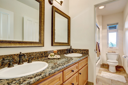 Double sink bathroom vanity with antique faucets and decorative candles on the top. Bathroom interior. Northwest, USA