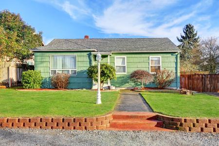 Green Suburban Bungalow style home on blue sky background. Northwest, USA