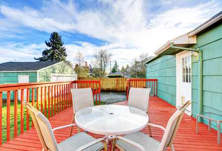 Red wooden walkout deck with table set, American bungalow house exterior. Northwest, USA