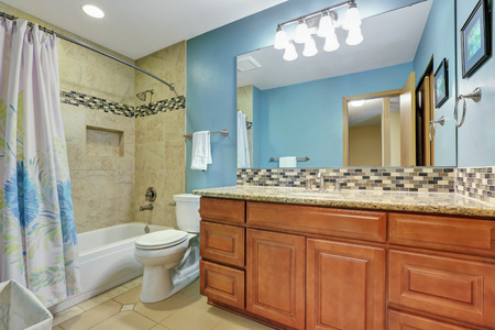 granite wall: Blue bathroom interior with mosaic back splash, beige tile wall trim and wooden vanity with granite counter top. Northwest, USA