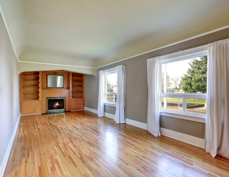 Unfurnished living room interior in old craftsman house. Gray walls, hardwood floors and fireplace. Northwest, USA