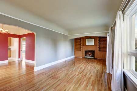 unfurnished: Unfurnished living room interior in old craftsman house. Gray walls, hardwood floors and fireplace. Northwest, USA
