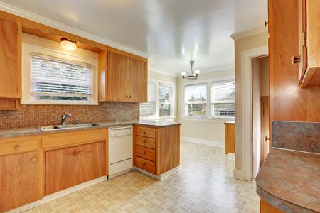 Bright kitchen room with od style wooden cabinets, linoleum floor. Northwest, USA