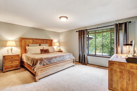 American Bedroom interior with queen size bed and wooden desk. Northwest, USA