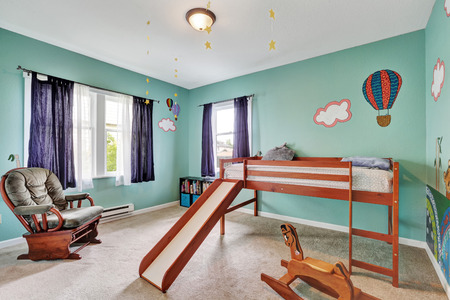 Cheerful kid's bedroom with green painted walls, wooden bed with slide and rocking horse. Northwest, USA