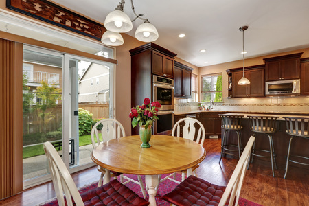 round chairs: Cozy kitchen and dining room interior with hardwood floor. Close up of round wooden dining table and four chairs with cushions. Northwest, USA