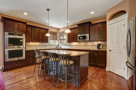 cabinets: Well remodeled kitchen room interior with dark wood cabinets, kitchen island with bar stools and pantry. Northwest, USA