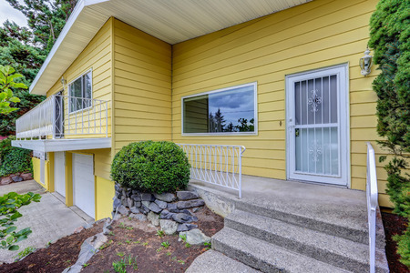 House exterior with yellow clapboard siding and concrete porch with stairs. Northwest, USA Stock Photo