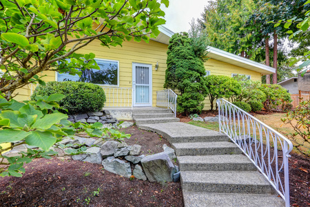 house windows: House exterior with yellow clapboard siding and concrete porch with stairs. Northwest, USA Stock Photo