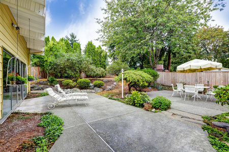 Backyard interior of yellow siding house. View of concrete floor, green bushes and outdoor furniture. Northwest, USA Stock Photo