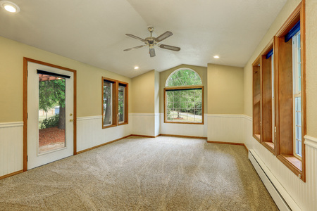 the vaulted: Empty living room interior in white and beige tones. Bright room with arched window, vaulted ceiling, carpet floor and glass door to the backyard. Northwest, USA