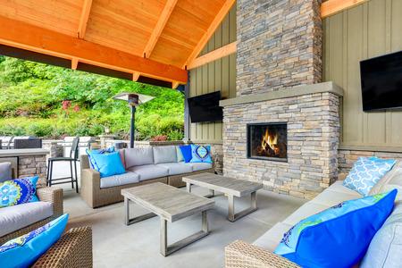 タコマ ローンテニス クラブの屋根付きのパティオ エリアのインテリアを募集します。石造りの暖炉、柳細工の家具、クッション ベージュと明るい