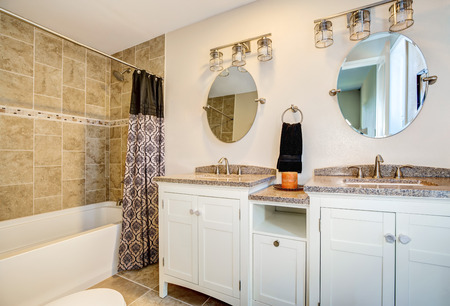 Bathroom detail. Vanity with dual sink and white cabinets, also tub and shower combination with brown tile wall trim and a curtain. Northwest, USA