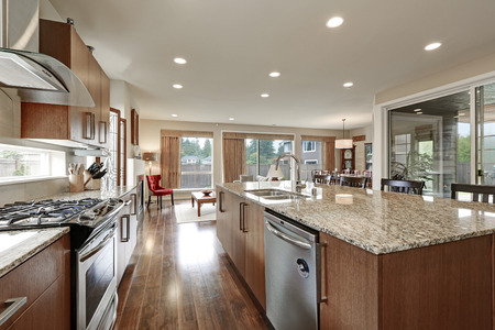 polished floors: Bright modern open plan kitchen room interior. Large bar style island with granite counter and polished hardwood floors. Northwest, USA