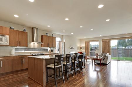 polished floors: Bright modern open plan kitchen room interior. Large bar style island with stools and polished hardwood floors. Northwest, USA
