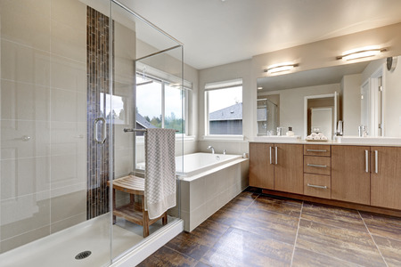 Cuarto de baño interior moderno blanco en la casa nueva. tocador de lavamanos doble con espejo grande, cabina de ducha, bañera blanco y el piso de baldosas de color marrón. Noroeste, EE.UU. Foto de archivo - 67378880
