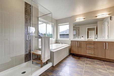 Weißes modernes Badezimmerinnenraum im nagelneuen Haus. Doppelwaschbecken mit großem Spiegel, ebenerdiger Dusche, weißer Badewanne und braunem Fliesenboden. Nordwest, USA Standard-Bild - 67378880
