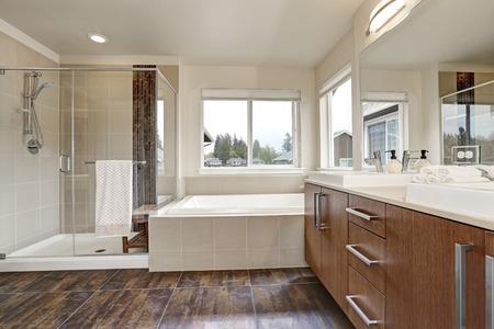 새 집에 흰색 현대적인 욕실 인테리어입니다. 대형 거울, 워크 인 샤워, 흰색 욕조 및 갈색 기와 바닥이있는 싱크대 세면대. 미국 노스 웨스트