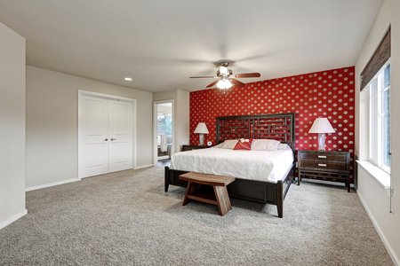 Master bedroom interior with large bed and red wall. Northwest, USA