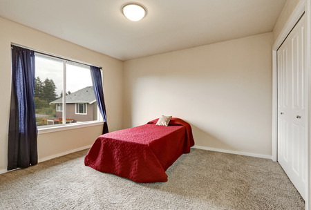 second floor: Single red bed in empty bedroom on the second floor of a new house. Northwest, USA