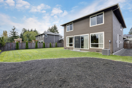 northwest: Grass filled back yard. Brown siding house exterior. Northwest, USA
