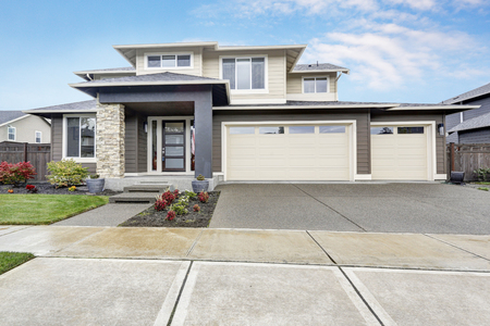 Curb appeal of brand-new home in brown and beige colors with two garages and concrete driveway. Northwest, USA