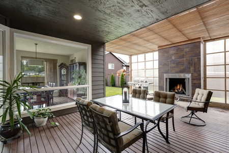 outdoor fireplace: Covered patio area in luxurious house. Furnished with glass top table and chairs with beige cushions, also there is fireplace and barbecue. Northwest, USA