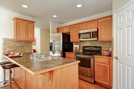 American Kitchen room in brown and white colors with backsplash tile, bar style kitchen island and pantry. Northwest, USA