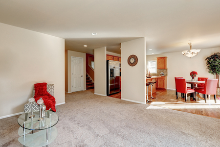 open floor plan: Typical American open floor plan interior design with carpet floor . Including interiors of living, dining and kitchen room, also hallway in the background. Northwest, USA Stock Photo