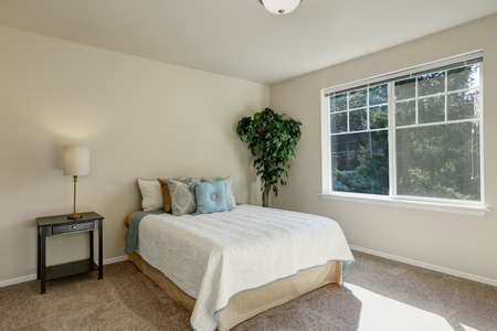 Simply furnished bedroom interior with neatly arranged pillows on the bed and sunlight coming through the window. Northwest, USA Banco de Imagens
