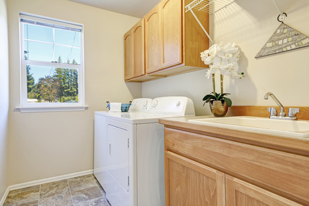 dryer  estate: Bright interior of laundry room with cabinets and white appliances. Northwest, USA Stock Photo