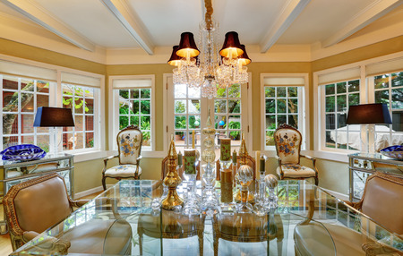 glass table: Lovely victorian style dining room interior with glass table , traditional old antique chairs and vintage classic design chandelier. Northwest, USA