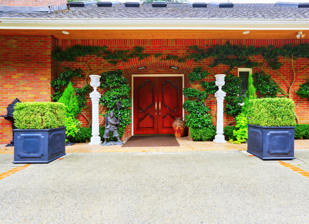 home and garden: Luxury house entrance overgrown with green plants front double door of solid wood, also decorated with nice vase and mans statue of a warrior. Northwest, USA