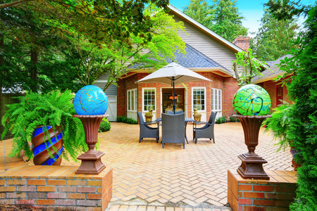 red brick: Luxury red brick house exterior. Paved patio with globe lights. Northwest, USA Stock Photo